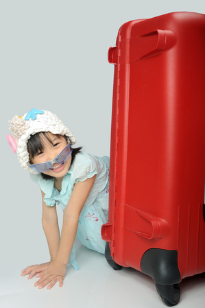 little asian girl in a weave hat and sunglasses sitting behind a huge travel red suitcase photo
