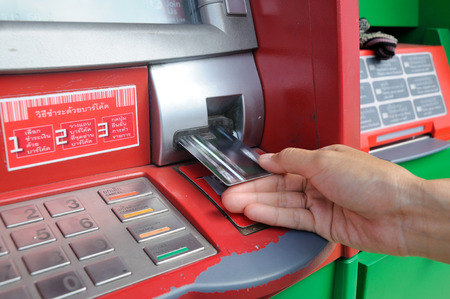 inserting card into an ATM to begin a financial transaction photo