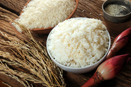 cooked rice, uncooked rice and paddy rice on wooden tabel; three varieties of rice photo