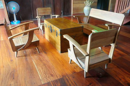 a vintage teak wood console table and armchair on wooden floor; asian style wood furniture photo