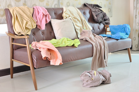 dirty clothes: Messy clothes scattered on a sofa in living room Stock Photo