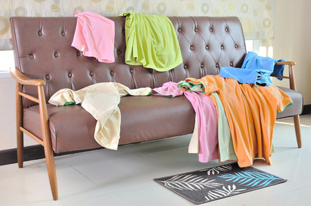 messy clothes: Messy clothes scattered on a sofa in living room Stock Photo