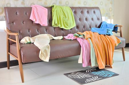 Slordig kleding verspreid op een sofa in de woonkamer Stockfoto