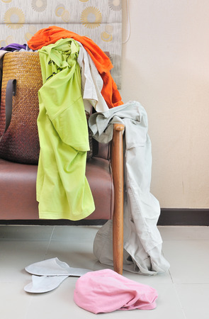 messy clothes: Messy clothes scattered on a leather sofa; housework concept