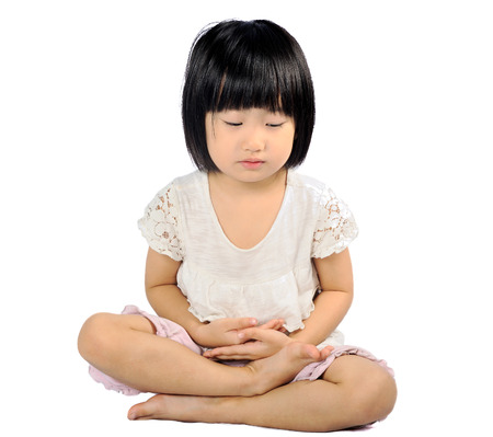 asian small child doing meditation in buddhism practice on white background photo