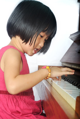 little asian child playing the piano and sing photo