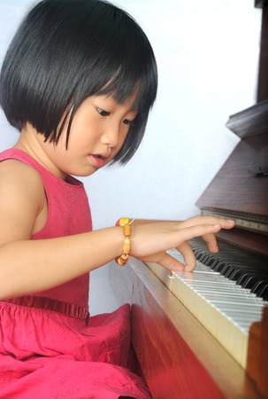little asian child playing the piano