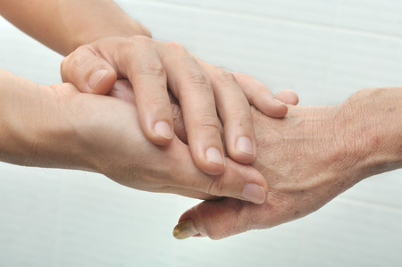 hands touch: Young male hand holding an old womans hand. Stock Photo