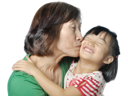 grandkid: Asian grandmother kissing her little granddaughters cheek