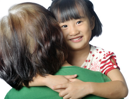 little asian granddaughter smiling in senior womans arm photo