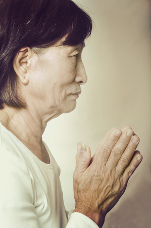 spirtual: old asian buddhist woman praying with her hands put together