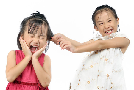 Siblings teasing, asian little girl pulling her sister