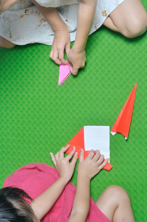 asian children make origami paper craft