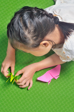 craftwork: asian child makes origami paper craft