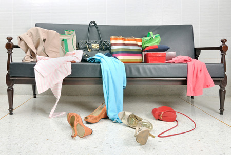 messy clothes: Messy clothes, lady bag and shoes scattered on a leather sofa