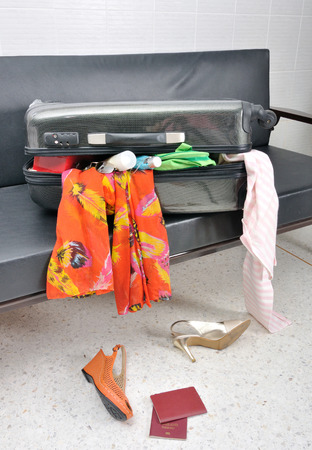 overfilled: stuff and clothes travel suitcase scattered in a sofa