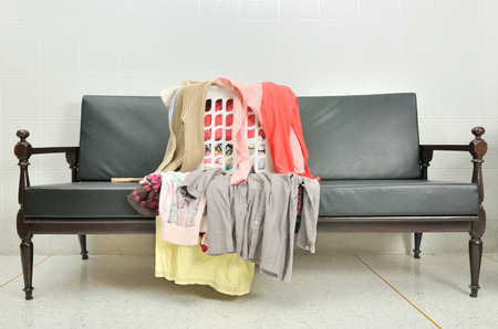 disorganized: a lot of clothes scattered in the basket on a sofa Stock Photo