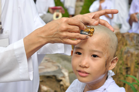 ordination: Buddhist little girl be removed hair to become a nun during a Buddhist ordination ceremony. Stock Photo
