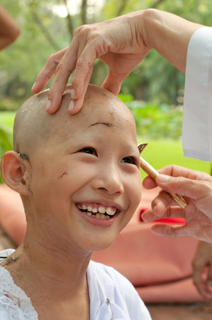 ordain: Buddhist little girl be removed hair to become a nun during a Buddhist ordination ceremony. Stock Photo