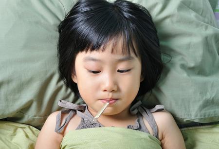 ragazza malata: Piccola ragazza asiatica malata sotto la coperta con la temperatura in bocca
