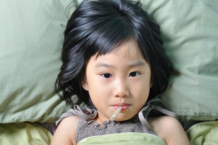 Niña enferma asiático bajo la manta con la temperatura en la boca