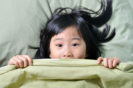 Scared little asian girl having childhood nightmares and hiding behind blanket Stock Photo