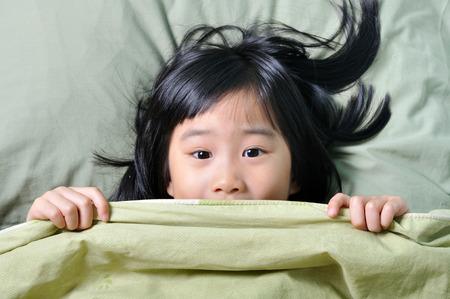 Scared weinig Aziatisch meisje dat de kindertijd nachtmerries en zich te verschuilen achter deken Stockfoto
