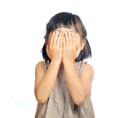 hide and seek: asian little girl cover her face with her hand isolated in white background Stock Photo