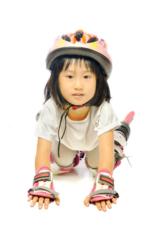 accidental: little asian girl in protective gear fell off while rollerskating isolated on white background