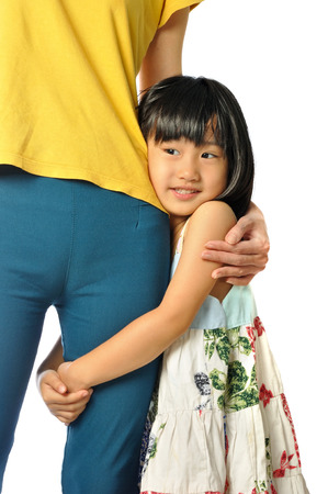 Asian little girl hugging mothers leg in the white background