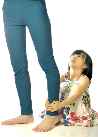 hugging legs: asian little girl hugging mothers leg and looking up her mother in the white background Stock Photo