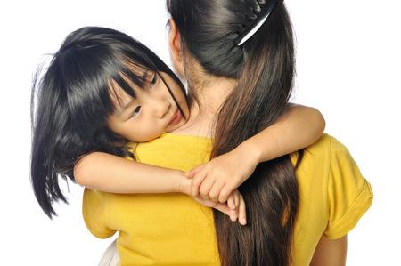 sad asian little girl hugging parent around shoulders on white background