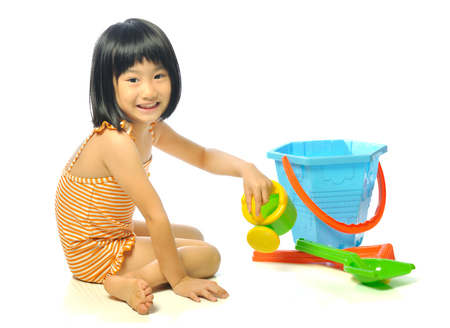 asian little girl in swimsuit playing with beach toys on white background