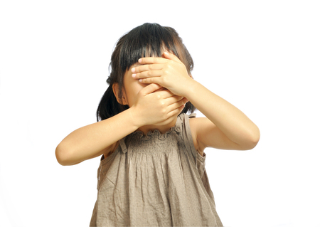 Close-up portrait of asian girl child with closed eyes and mouth with her hands over white background. concept of empty mind.