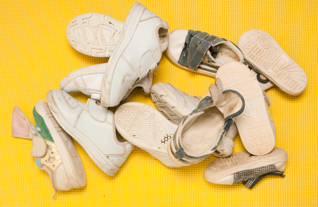 medium size: Used cluttered kid shoe in different size from  baby size to girl size representing growth, education concept in the yellow background