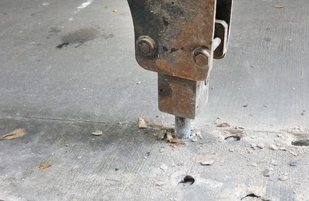 油圧ショベルの掘削機によるコンクリートの道路を掘削 写真素材