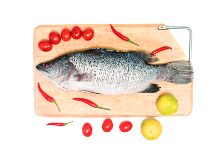 Fresh raw Asian Sea Bass fish  on wooden cutting board with lemon, tomato and chilli on white background, top view. Seafood asian cooking ingredients.