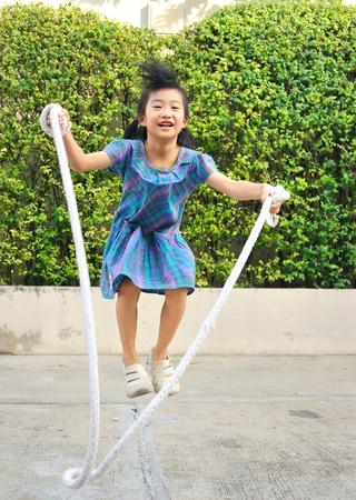 Retrato de niña asiática saltando cuerda hecha a mano entre columpios en el parque.Enfoque selectivo.