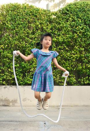 Retrato de niña asiática saltando cuerda hecha a mano entre columpios en el parque.Enfoque selectivo. Foto de archivo