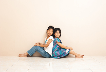 Cute smiling asian siblings sit and touch each other with their backs. Lovely sincere emotions from childhood.
