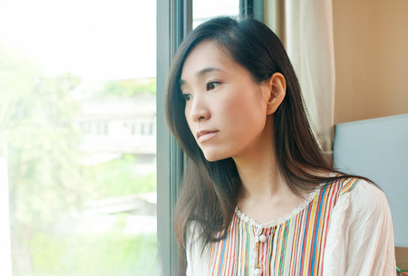 Young asian woman  looking through window at home. Stock Photo