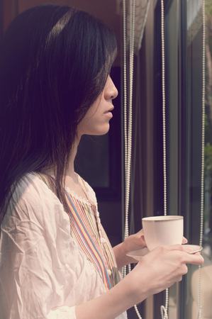 Asian woman look pensive and lonely through window with a cup of coffee or tea in vintage style.