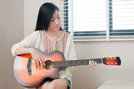 Smiling asian beautiful girl sitting in the music room while playing guitar, leisure concept. Stock Photo
