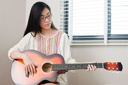 Asian beautiful girl wearing eyeglasses and sitting in the music room while playing guitar, leisure concept. Stock Photo