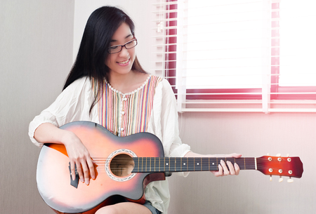 Smiling asian beautiful girl sitting in the music room and playing guitar and leisure concept.