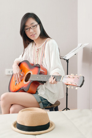 Smiling asian beautiful girl sitting in the music room and playing guitar, leisure concept. Stock Photo