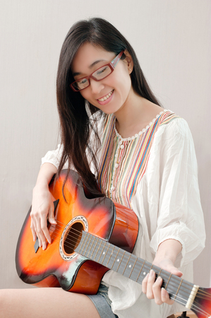 Smiling asian beautiful girl wearing eyeglasses and playing guitar in the music room, leisure concept. Stock Photo