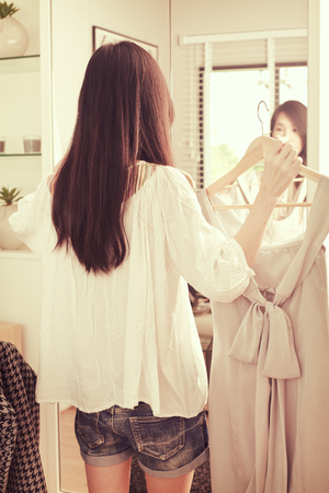 Young asian woman choosing clothes in front of the mirror. Stock Photo
