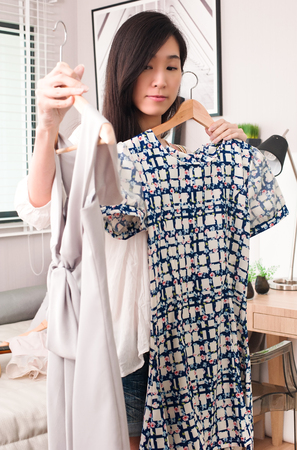 Confused young asian woman trying to choose dresses standing in the room. Selective focus. Stock Photo