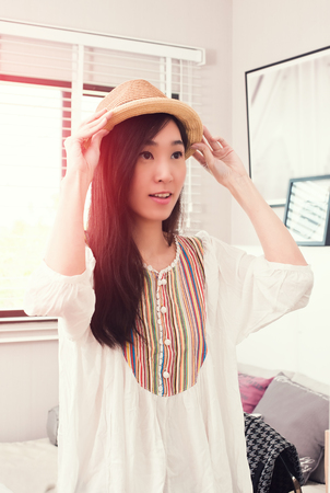 Beautiful Asian woman trying panama hat in front of mirror.